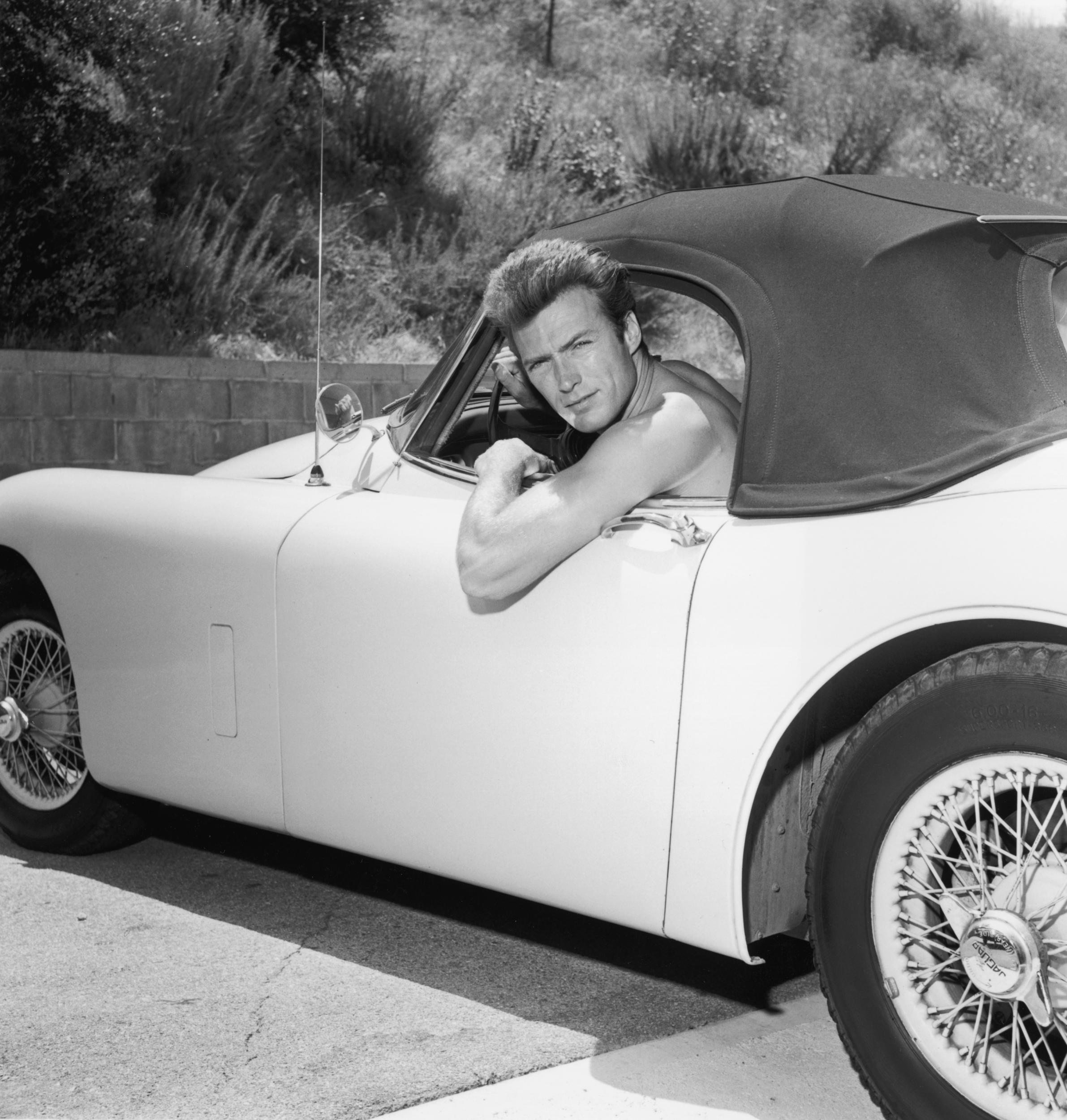 Small car for a big guy. A shirtless Clint Eastwood strikes a pose with his Jaguar convertible, circa 1965.