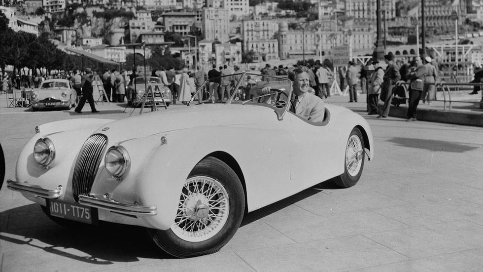 American actor Van Johnson, who became very popular during the war due to the absence of the establisted leading men, poses in his Jaguar XK120 parked in a croweded square.