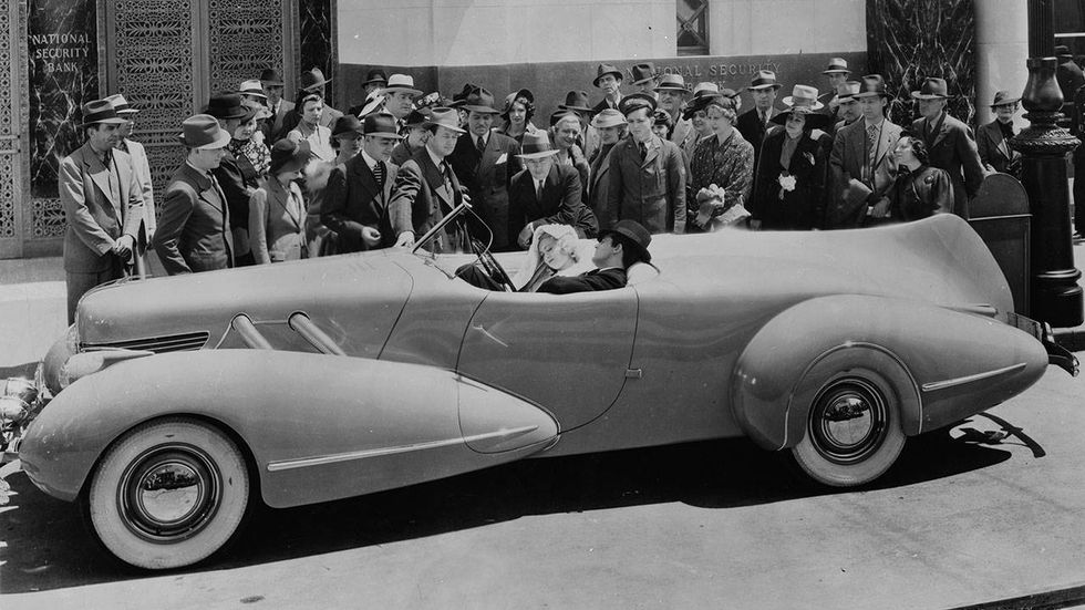 1937: Brithish born actor Cary Grant (1904-1986), and American actress Constance Bennett (1904-1965), stars of the film 'Topper' directed by Norman Z McLeod, ignore the crowd gathered around them as they drive in the Topper Buick.