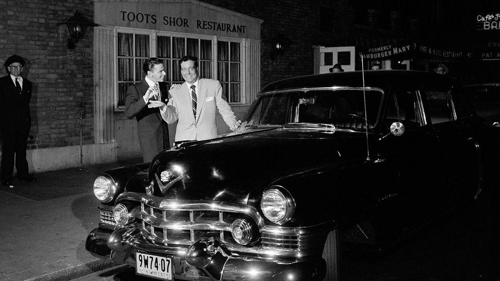 American singer and entertainer Frank Sinatra(1915-1998)(center) hands the keys of his Cadillac to actor and entertainer Jackie Gleason(1916-1987)(right) on the street in front of the celebrity watering-hole Toots Shor's Restaurant. New York, New York, October 16, 1951
